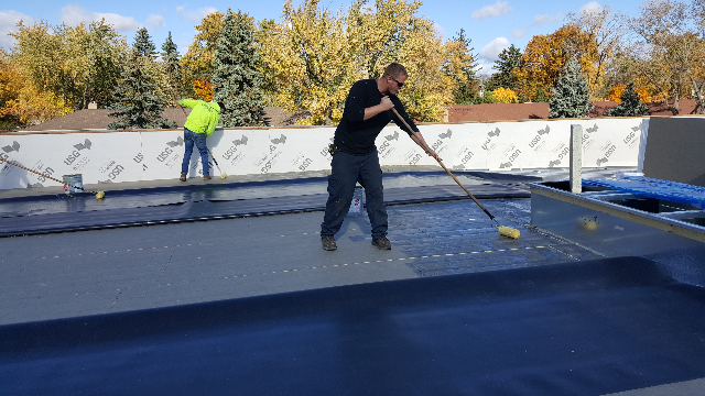 Installing and fully adhering the new TPO membrane.