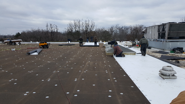 Installing the new TPO membrane.