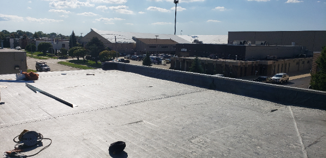 Inspecting commercial roofing project